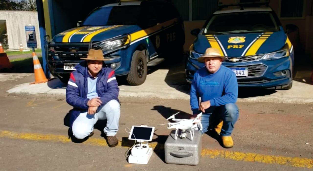 foto colorida horizontal mostra os dois professores de chapéu, agachados, à frente de dois carros da PRF estacionados, e na frente deles o drone e um monitor