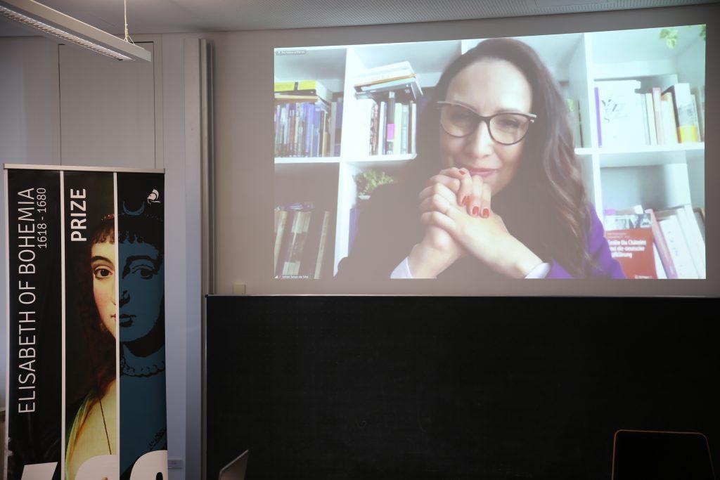 foto colorida horizontal mostra um telão com a imagem da professora, com as mãos unidas junto ao queixo, e do lado um banner da premiação