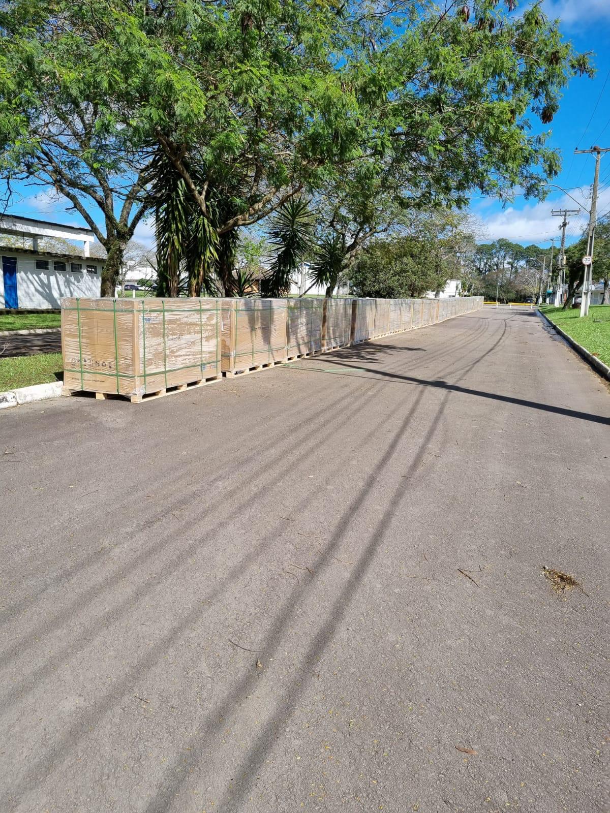 foto vertical colorida mostra uma rua asfaltada do centro de eventos, e sob árvores estão alinhadas várias caixas de grande porte com os equipamentos a serem instalados