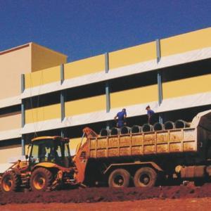 Foto horizontal colorida de prédio de 4 andares amarelo com branco e azul, na frente chão de terra vermelha, um trator e um caminhão com 2 trabalhadores em cima