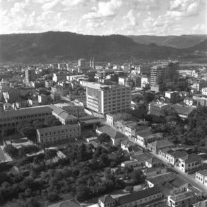 Fotografia quadrada preto e branca da vista aérea da Rua Marechal Floriano Peixoto e entorno em Santa Maria, com a construção dos prédios das Faculdades de Farmácia e Medicina, ao fundo morro coberto por vegetação.
