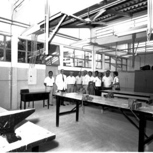 Fotografia horizontal preto e branca da Inauguração das novas instalações do Colégio Industrial. Em um ambiente amplo, três mesas retangulares de madeira. No centro ao fundo da imagem, um grupo de 12 homens. Vestem roupas claras.