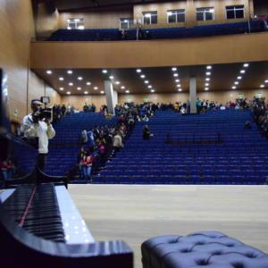 Fotografia horizontal colorida da Inauguração do Centro de Convenções da UFSM. Em ambiente interno, foto tirada de cima do palco. A esquerda, um piano. Atrás dele, um homem segura uma filmadora com as mãos e aponta em direção ao palco. Ao fundo, cadeiras azuis e mezanino. Inúmeras pessoas estão pelos corredores.