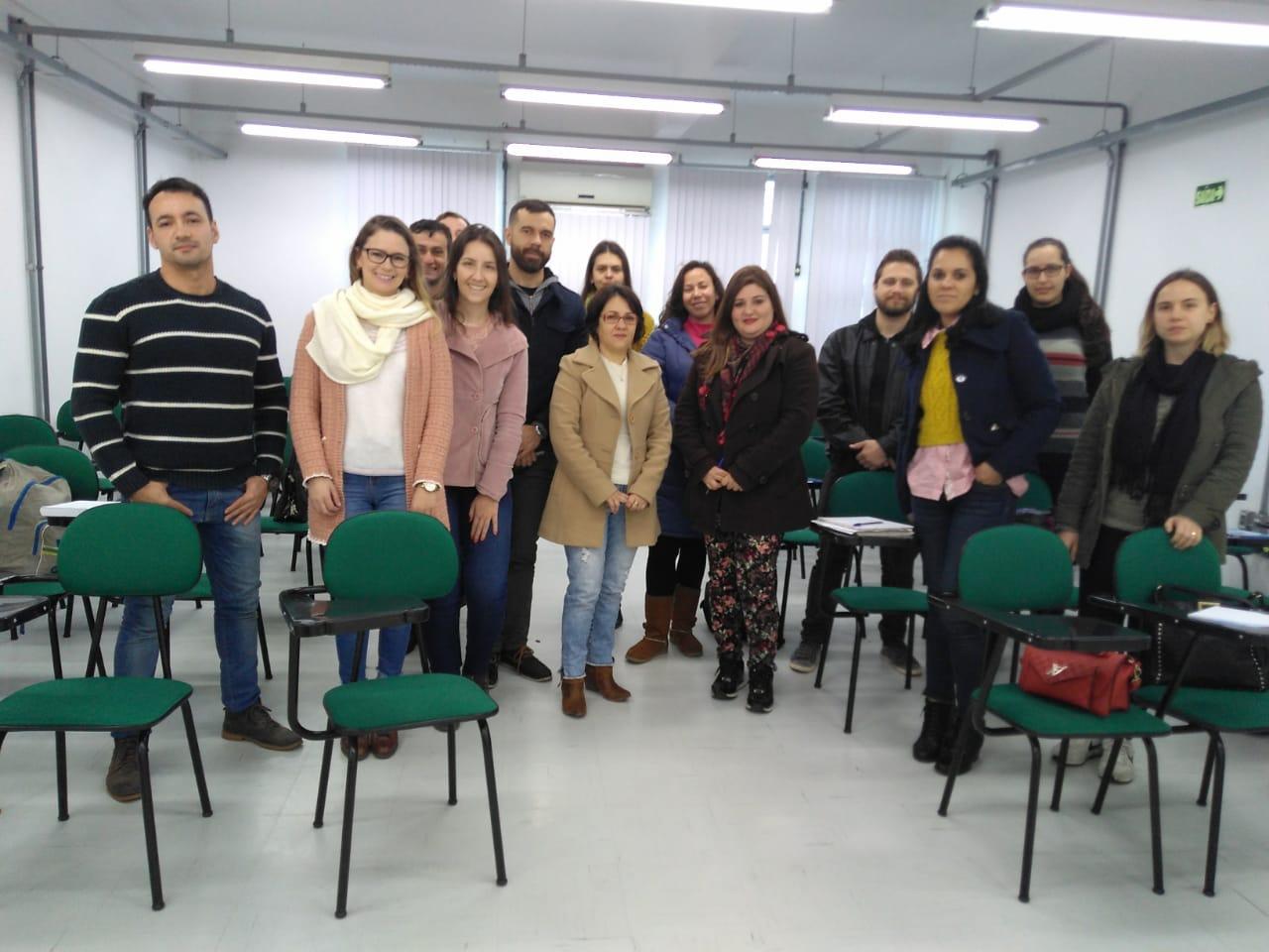 Foto mostra 14 servidores em pé, lado a lado, em uma sala de aula com cadeiras verdes
