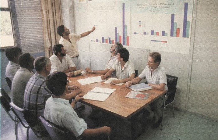 Imagem antiga de homens sentados em uma sala olhando para um gráfico.