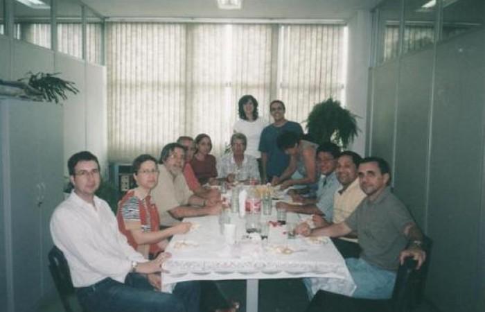 Imagem antiga de pessoas em volta de uma mesa.