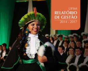 Capa Relatório de Gestão 2014 a 2017 com estudante indígena vestida com beca preta e cocar verde na colação de grau