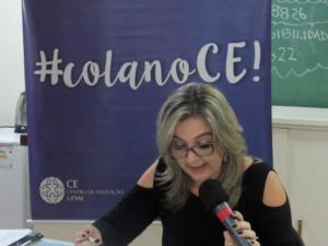 """Foto horizontal. Uma professora com um microfone na mão e braços apoiados em uma mesa branca. Atrás dela há um banner escrito """"#colanoCE"""""""