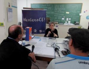 Foto horizontal. Uma professora sentado com um microfone na mãe. Em sua frente, há dois homens, também segurando microfones. Entre eles há uma mesa branca.