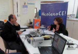 Foto horizontal. Uma professora está sentada em uma cadeira, segurando um microfone. Em sua frente há um jornalista segurando um microfone.  Entre eles há uma mesa branca com equipamentos de gravação e um notebook.