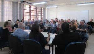 Fotografia horizontal tirada do fundo para a frente da sala. Dois homens e duas mulheres compõe a mesa de palestrantes e estão voltados para um grupo de pessoas sentadas a frente.