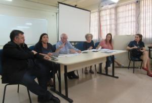 Imagem horizontal tirada do canto da sala. Mesa com os representantes da PROGRAD e PRPGP e Direção do CE. Sentada ao lado direito da mesa a Secretária da Direção.