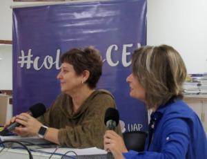 Foto horizontal. Duas professoras estão sentadas lado a lado sendo entrevistadas. As duas seguram um microfone.