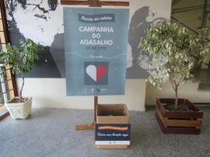 fotografia horizontal e colorida de um banner em um suporte de madeira, a frente uma caixa de papelão e nas laterais dois vasos de plantas, um em cada lado da imagem.