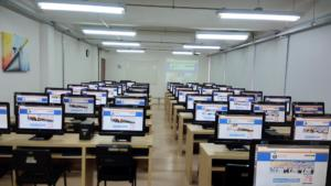 Duas fotografias horizontais tiradas da frente para o fundo da sala, de um laboratório de informática. Há três computadores - na cor preta, por mesa - da cor bege, enfileirados do início ao fim da foto. Na parte superior, aparecem lâmpadas acesas na cor branca, também enfileiradas, e na parede do lado esquerdo há um quadro colorido pendurado.