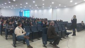 Auditório cheio de novos alunos e alunas. Está em pé a pedagoga do Centro de Tecnologia, segurando um microfone.