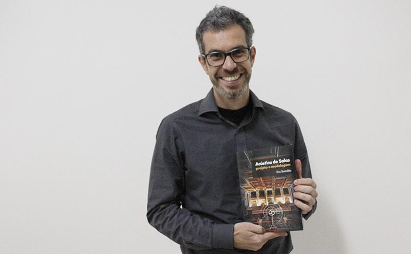 """Professor Eric Brandão segurando o livro """"Acústica de Salas"""", do qual ele é autor."""