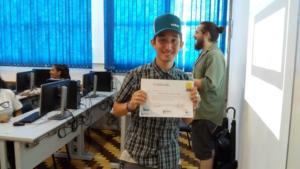 Garoto em uma sala com computadores ao fundo, segura sorridente um certificado.
