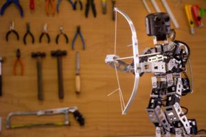 Um pequeno robô está de pé, segurando um arco e flecha.