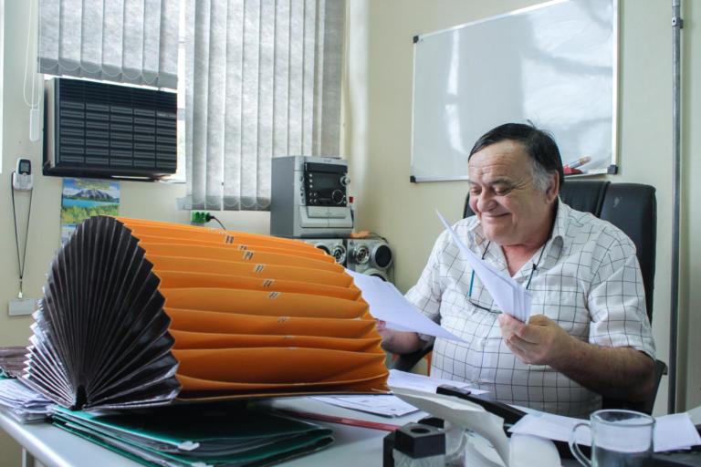 Senhor idoso sentado, segurando papéis, sorrindo. Em primeiro plano está uma mesa repleta de papéis sobre ela.