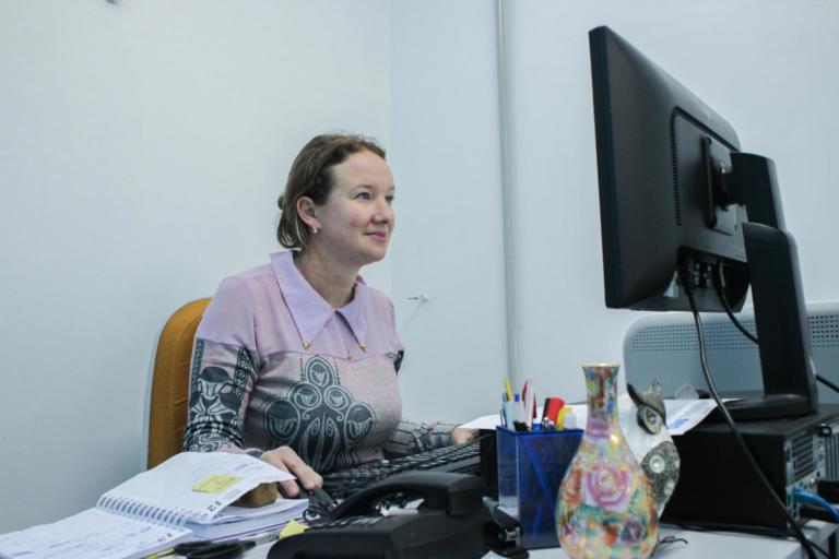 Mulher sentada em frente a uma mesa. Uma das mãos está no mouse, ela olha para a tela do computador que está sobre a mesa.