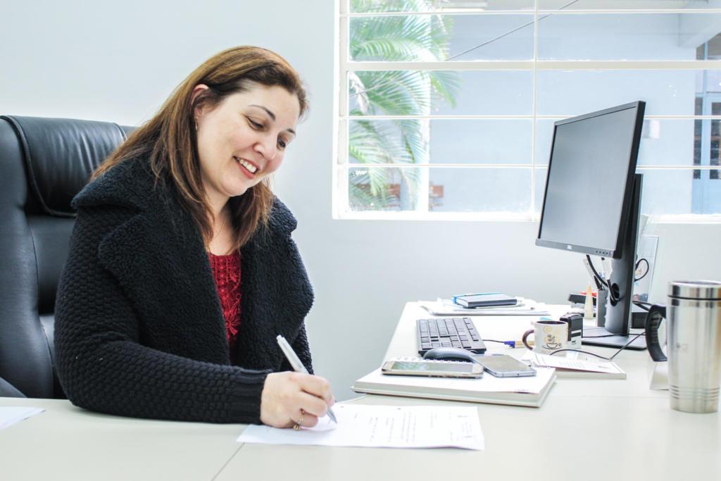 Mulher sentada escreve em papel sobre uma mesa.