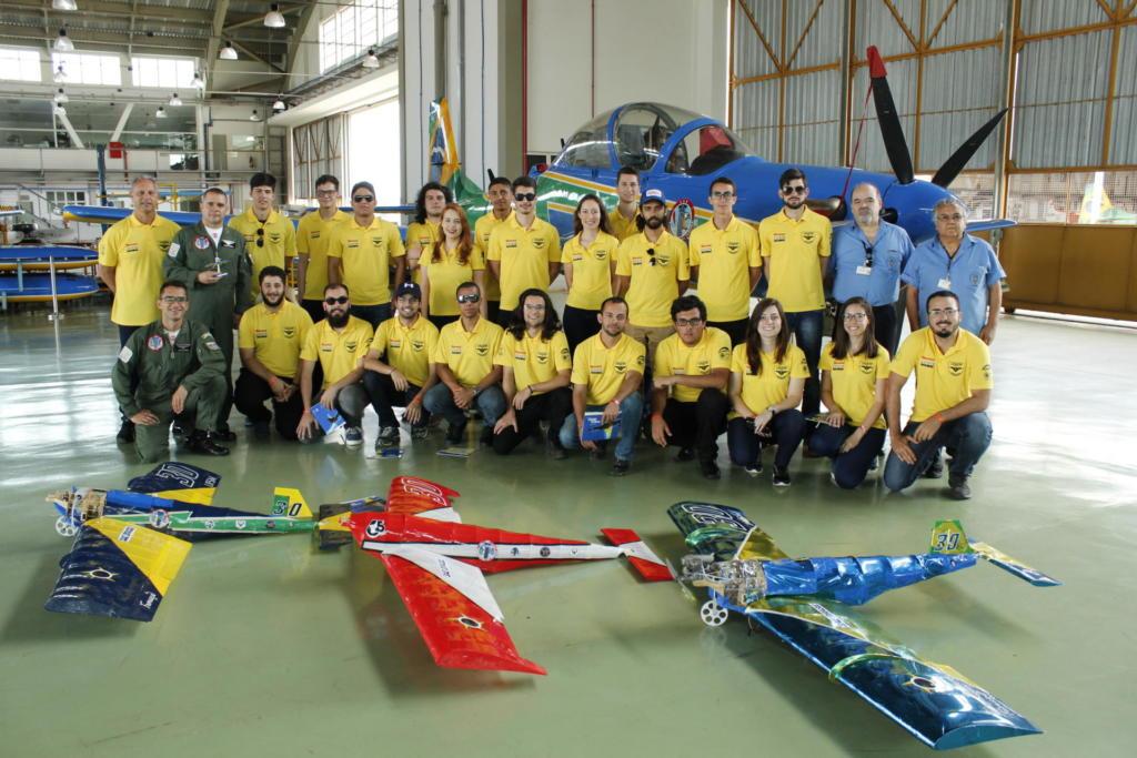 Equipe Carancho reunida. A frente estão três dos modelos de aviões que já projetaram.