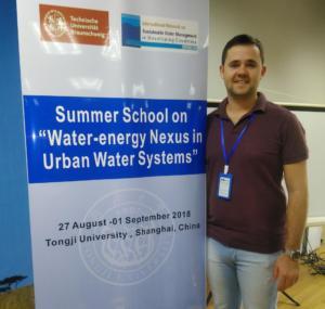 """Homem com um crachá de pé ao lado de um cartaz com a frase """"Summer School on 'Water-energy Nexus in Urban Water Systems'"""""""