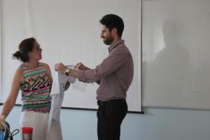 Um homem está de pé, entregando uma camiseta braca a uma mulher, que está de pé ao seu lado.
