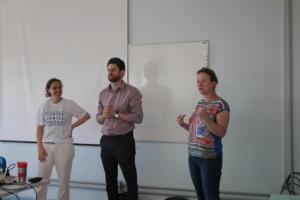 Um homem e duas mulheres estão de pé, lado a lado, em frente a um quadro branco.