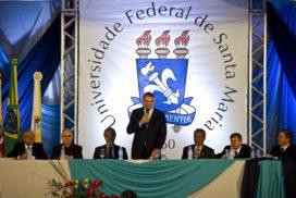 Uma mesa com sete homens. Ao fundo, uma banner com a logo da UFSM. O homem no centro da mesa está em pé, falando com um microfone em sua mão direita.