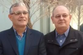 Dois senhores, lado a lado, vestidos de terno preto. À esquerda está o professor José Mario. À direita está o professor Hilton Grüdling.