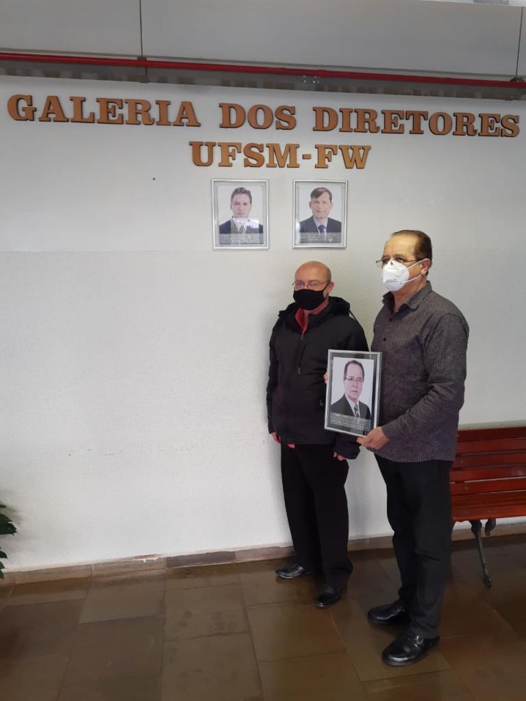 Na imagem, da esquerda para a direita, aparecem o professor Bráulio Caron, atual diretor da UFSM-FW, e o professor Lauro Chielle, primeiro diretor Pro Tempore da UFSM-FW, segurando a foto do professor Lauro. A imagem foi registrada em frente à Galeria de Diretores da UFSM-FW.
