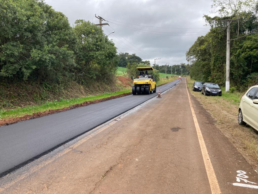 Imagem do trecho de acesso à UFSM-FW. Aparecem na imagem, à direita, parte da estrada com asfalto antigo, e à esquerda, máquina realizando trabalho na massa asfáltica recém colocada.