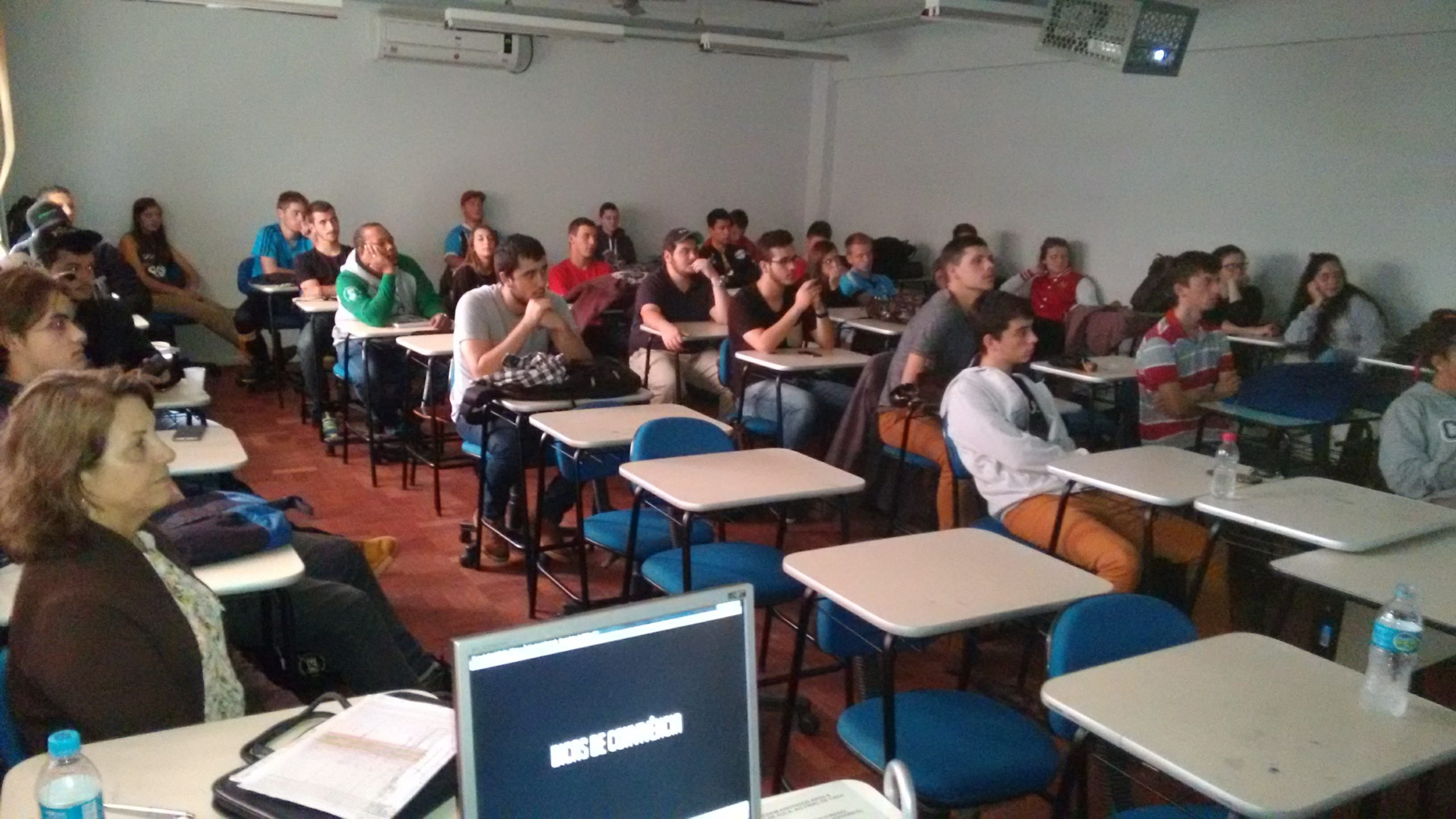 Descrição da fotografia: Alunos sentados nas cadeiras em fileiras, alguns debruçados nas classes. Todos olham na mesma direção.