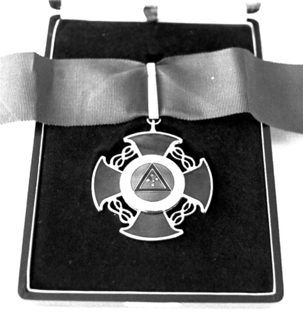 Fotografia em preto e branco. Em uma base retangular de veludo escuro, deita uma medalha. Tem formato arredondado, com quatro folhas em formato triangular, com bordas em contorno branco. Interligando as folhas, há fios trançados na cor branca. Ao centro dela há um círculo branco emoldurando um triângulo, onde aparecem as estrelas do Cruzeiro do Sul. Ela possui uma fita larga em sua presilha.