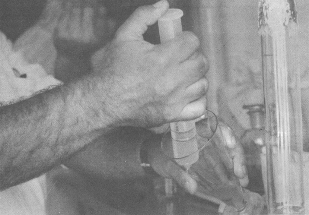 Fotografia em preto e branco. Mãos de homem com a pele clara manuseando uma seringa grande e um copo. No pulso esquerdo aparece a pulseira de um relógio. Ao redor vêem-se tubos de ensaio e materiais de química. Ao fundo e acima aparece a mão de outra pessoa.