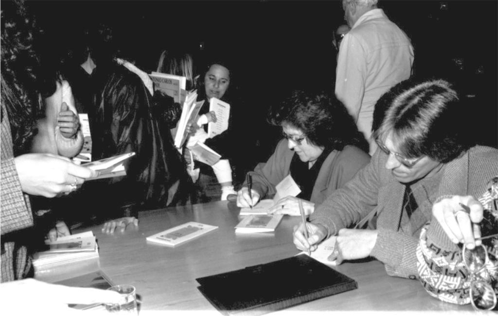 Fotografia em preto e branco. Várias pessoas reunidas ao redor de uma mesa com livros e uma pasta preta. À esquerda da imagem há pessoas em pé segurando livros. Ao centro há uma mulher e um homem sentados escrevendo. Os dois usam óculos e vestem-se formalmente. À direita aparece a mão direita de uma pessoa segurando um óculos e entre seus dedos há uma caneta. Ao fundo há pessoas sentadas e em pé.
