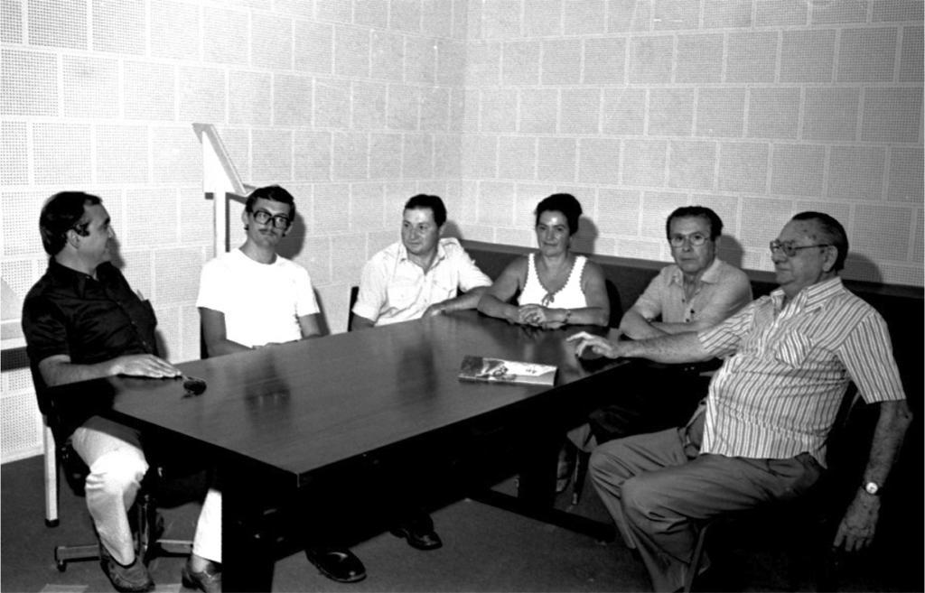 Fotografia em preto e branco, em plano geral, de cinco homens e uma mulher sentados ao redor de uma mesa retangular escura. Sobre a mesa, um óculos de sol e um folheto. Ao fundo, parede de revestimento acústico branco e um púlpito.