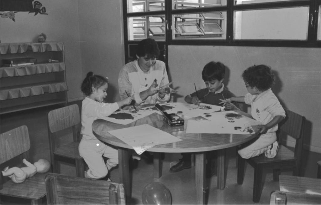 Fotografia em preto e branco de uma sala com uma mulher e 3 crianças sentadas ao redor de uma mesa baixa com pincéis, tintas e folhas de papel contínuo. A mulher está ao centro com as mãos sobre a mesa segurando um vidro pequeno de tinta e sorrindo. À direita da mulher, uma menina sentada na ponta da cadeira, encostada com o peito na mesa, segura o pincel sobre a folha e olha a pintura com a boca entreaberta. À direita da mulher, um menino segura o pincel com a mão direita e deixa a esquerda sobre a mês,a próximo a um vidro de tinta, enquanto o menino à direita se estica e enfia o dedo anelar da mão direita no vidro e com a esquerda segura o tampo da mesa. Ele está ajoelhado na cadeira. Ao fundo, parede com desenho, estante, porta e janelas de vidro. Sobre a cadeira, próximo à menina, um boneco sem roupas deitado. Embaixo da mesa, um balão cheio.