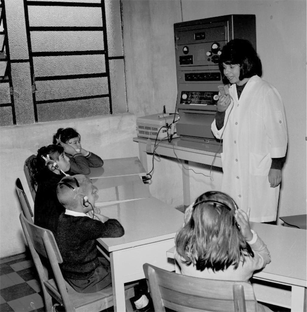 Fotografia em preto e branco e formato paisagem de um ambiente interno com uma mulher em pé segurando um microfone em frente a quatro crianças em carteiras escolares, com fones de ouvido supra-auriculares. Ao centro, vê-se o canto da sala com uma mesa retangular à direita, com aproximadamente um metro de largura, e sobre ela dois equipamentos de som. O primeiro equipamento é quadrado, baixo, claro e tem um fio curto ligado ao microfone. O segundo é retangular, alto, escuro e tem botões claros. A mulher, à direita, tem pele clara, cabelos pretos com corte chanel e franja, e veste jaleco branco, longo, abotoado, de meia manga, sobre uma blusa escura. As crianças, três meninos e uma menina, têm pele clara e estão sentadas, lado a lado, em perspectiva, com as carteiras levemente em curva sobre as quais apóiam os cotovelos. À esquerda, o primeiro menino com cabelos escuros, testa franzida e mãos em forma de concha sobre os fones. Ao lado, o segundo, com cabelos escuros e lábios apertados. O terceiro tem cabelos claros. Eles usam cabelos curtos, roupas escuras e olham para a mulher, virados para a direita. A menina, ao lado e à direita, está de costas com as mãos sobre os fones, tem cabelo escuro na altura dos ombros, veste roupa clara e tem um foco de luz atrás de si. As paredes são claras. Na parede da esquerda, uma janela basculante alta.
