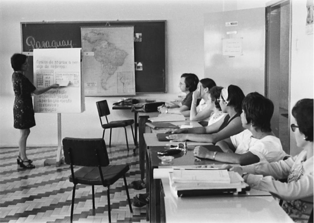 """Fotografia horizontal em preto e branco de um grupo de seis mulheres que olham para outra próxima a um bloco de flip-chart em sala de aula. Todas têm pele clara, cabelos escuros e curtos, exceto uma que está com o cabelo preso. A mulher sozinha está em pé, à esquerda, de perfil, virada à direita, usa vestido escuro, acima dos joelhos, estampado, de manga curta, sandálias pretas e mostra uma linha de um quadro no bloco de flip-chart, com um retângulo branco, que segura com a mão direita. No topo da folha, """"Ensino de 3º grau a serviço da reforma"""". No centro, dois quadros, lado a lado e abaixo, uma lista com cinco itens. O bloco está sustentado por uma barra horizontal e um pé central e, localiza-se à frente de um quadro-negro. O grupo está à direita, em fila única, todas sentadas, viradas à esquerda, com os braços apoiados sobre as carteiras escolares claras. Sobre as mesas, livros, cadernos, pastas, óculos, carteira e um cinzeiro. Em frente às mesas, uma cadeira. Ao fundo, paredes claras, parte do quadro-negro com a palavra Paraguay na cor branca, um mapa da América do Sul pendurado e duas fotos. À direita, abaixo do quadro, uma carteira escolar e uma cadeira. Atrás do grupo, uma porta aberta com letreiros de onde se vê o corredor. No chão, listras diagonais de parquê em tons alternados de claro e escuro."""