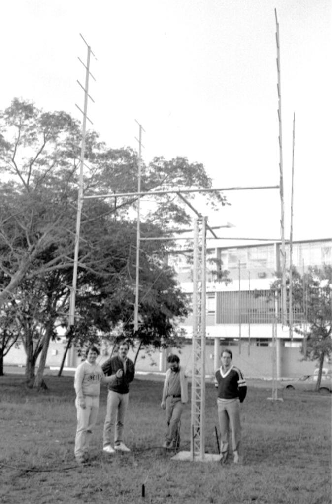 Fotografia vertical em preto e branco de quatro homens embaixo de uma antena metálica em um gramado. Ao centro, sobre um quadrado de concreto, uma torre retangular vazada de cerca de cinco metros de altura por vinte centímetros de largura, que sustenta uma estrutura horizontal em forma de H maiúsculo. Em cada uma das quatro pontas, uma haste na vertical fixada pelo meio, com cerca de cinco metros, com doze pequenas varetas paralelas na horizontal, seis para cima e seis para baixo. Próximos à torre, três homens à esquerda e um à direita. Eles estão de frente, têm pele clara, cabelos curtos e escuros. O primeiro veste camisa, blusão e calças claras e tem, à frente do peito, a mão esquerda fechada com o polegar estendido para cima. Ao lado dele, outro usa óculos, bigode e veste jaqueta escura, calça clara e calçado branco. Um pouco afastado, escorado na torre, homem com camisa e calça escuros e casaco claro aberto. Do outro lado, homem com óculos, blusão escuro com detalhes claros e calça escura. Ao fundo, árvores, rua horizontal com dois carros e prédio de dois andares, o qual ocupa a largura da foto.