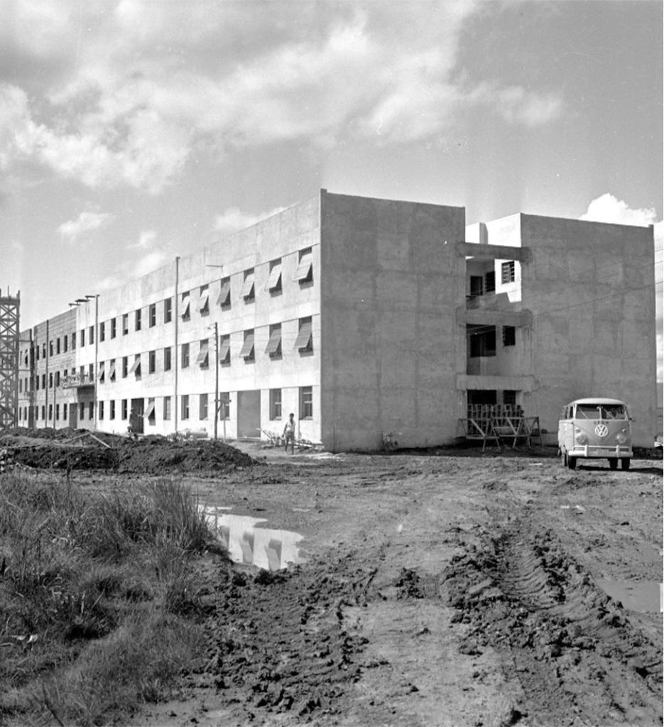 Fotografia quadrada, em preto e branco, de prédio de três pavimentos em construção em dia ensolarado. A foto está dividida em terços horizontais, o céu com nuvens, o prédio e a terra com marcas de pneus. Ao centro, a quina do prédio, do qual se vê a fachada frontal iluminada pelo sol, à esquerda, e a lateral sombreada, à direita. O prédio possui dois blocos paralelos, integrados por três vigas na lateral, com cerca de dois metros de largura e meio metro de altura. Está rebocado do meio da fachada até a quina e na lateral. Tem três fileiras com cerca de 30 janelas verticais cada e cinco entradas, dispostas simetricamente em toda a fachada. Na parte sem reboco, encontram-se apenas os vãos das janelas e na parte rebocada, quinze estão abertas, com a parte inferior projetada para fora e algumas somente com os vidros. À esquerda, em frente a uma parte sem reboco, uma torre escura, com aproximadamente a altura do prédio, semelhante a um andaime. Ao lado, um depósito de terra com cerca de meio metro de altura que se prolonga, à direita, até próximo à quina do prédio. Entre a terra e a parte do prédio rebocado, dois homens, um de frente, perto da quina, e o outro de costas, ao fundo. Na lateral, no vão entre os blocos, uma grade e andaimes. À frente, uma Kombi clara, de frente, com teto, para-choque e símbolo circular com um V centralizado sobre um W, em branco. No chão, à esquerda, mato alto e uma poça de água que reflete três janelas abertas. À direita, outra poça menor com o reflexo de parte da lateral do prédio.