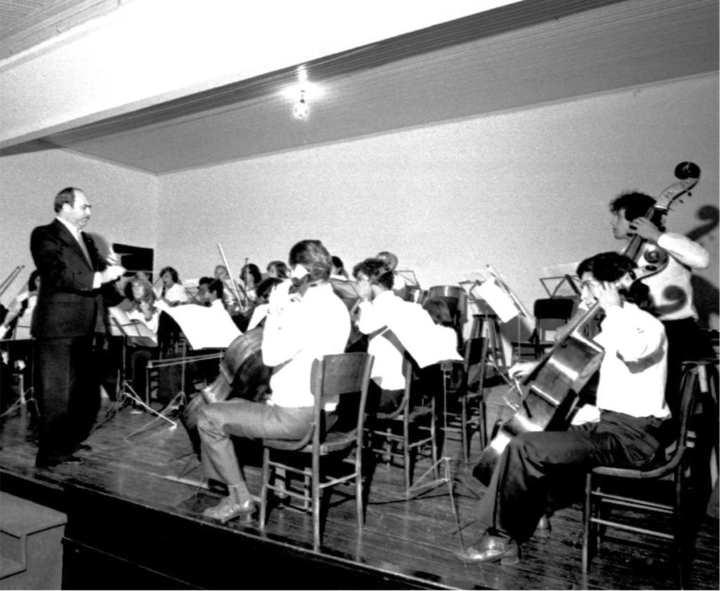 Fotografia horizontal em preto e branco de orquestra sobre um palco em uma sala. O regente está à esquerda, em pé, de perfil, virado à direita, é parcialmente calvo, tem cabelos, sobrancelhas e bigode escuros. Usa terno escuro sobre camisa branca, gravata clara e sapato escuro. Está com as mãos à frente do peito e segura uma batuta com a mão direita, a qual aponta para frente. Os músicos estão sentados em cadeiras de madeira, dispostos em semicírculo e usam camisas claras e calças escuras. Atrás do regente, na lateral esquerda, arcos de violino e lado direito de uma mulher. À direita do regente, ao fundo, pedestais com partituras e cerca de dez músicos, alguns com arcos. Do meio à direita, quatro músicos de perfil, virados à esquerda. Dois violoncelistas à frente, no centro da foto; um violoncelista e um contrabaixista ao fundo, na lateral direita. O palco de madeira é alto, escuro e tem uma escada, da qual se vê dois degraus da base do palco até o canto inferior direito. Ao fundo, forro rebaixado com uma luminária e paredes brancas e uma porta escura.