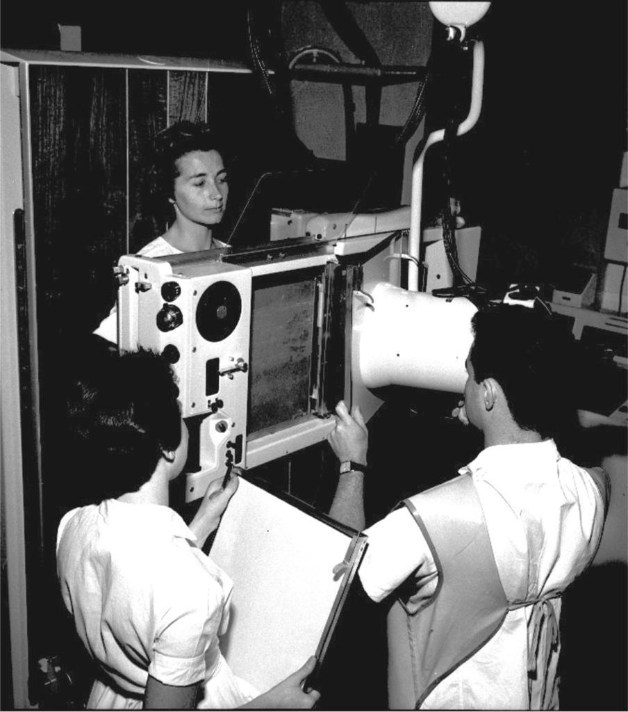 Foto vertical em preto ebranco deduasmulheres eumhomem, em plano médio, no entornodeumequipamentode radiografia. Uma das mulheres, àesquerda, de pé e decostas, segura àfrentedocorpo um chassi radiográfico (objeto com bordas metálicas de aproximadamente 30x40cm). Ela tem cabelos curtos, pretos,pele clara e usa umvestido acinturado, branco, demangascurtas. O homem,à direita,também de pée de costas,está em frente ao equipamentoradiográfico,comas mãos apoiadas em uma abertura na base esquerda. Ele tempeleclara, cabelos pretose curtos, veste camisa branca e avental dechumbo,em tom cinza. Noseu pulsoesquerdo, umrelógiocomvisor quadrado branco epulseira preta. De frente para o homem, atrás emanuseando o equipamento deradiografia,posicionada depé, uma mulher depeleclara, decabelo curto e escuro. Enxerga-seapenas pequenos detalhesde suaroupa branca, nos ombros e no braço direito. Oequipamento éretangular e horizontal, branco, comuma abertura vertical àdireita e, à esquerda,botões escuros dediferentes tamanhos. Adireita doequipamento, fiações deeletricidade, parte de outros equipamentos e,ao fundo, fora de foco, um armário que encobre parte da parede.