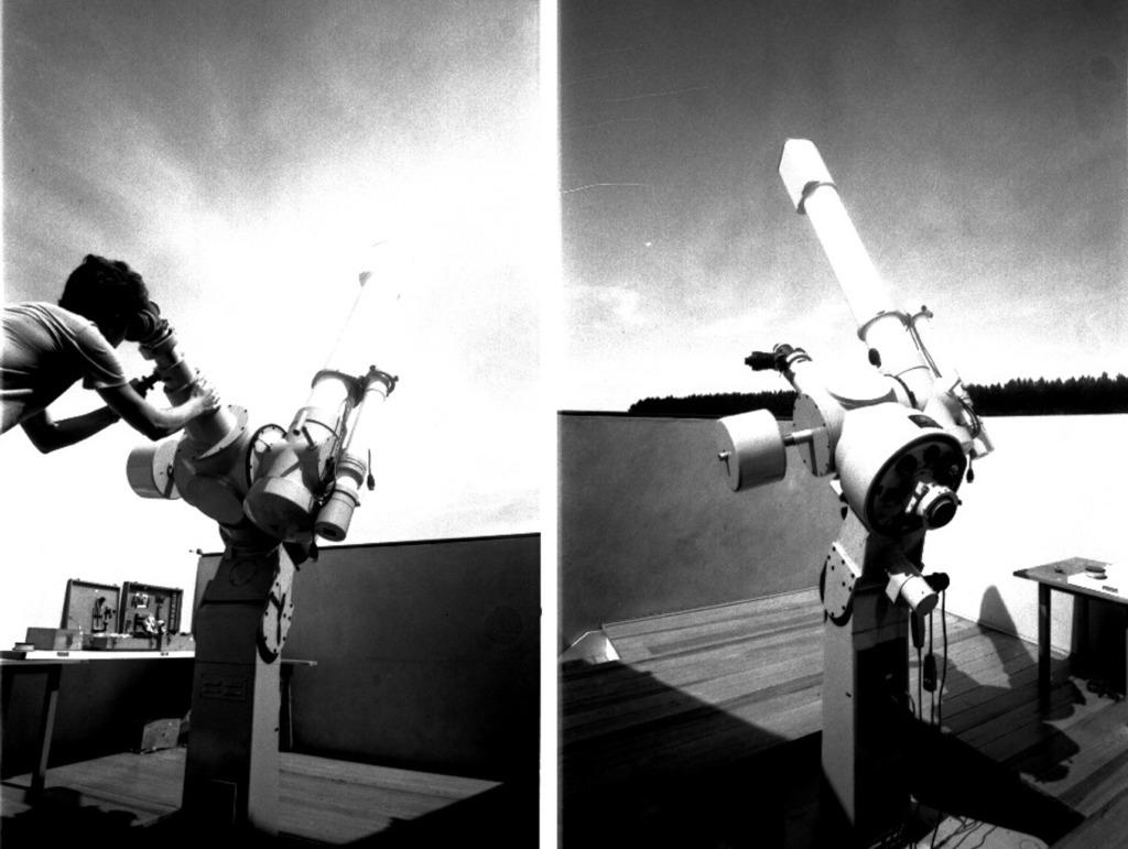 Audiodescrição da Imagem: Montagem horizontal de duas fotografias verticais, em preto e branco, postas uma ao lado da outra, de um homem que olha o céu através de um telescópio, em ambiente externo. Na imagem à esquerda, em um terraço, fixado no chão, o Telescópio Refrator Zeiss suportado por um grande e largo tripé de metal e engrenagens, levemente voltado para baixo, de aproximadamente um metro de altura. O telescópio é de um tom claro e composto por tubos em diversos tamanhos, e outras partes como: montura, buscador, tubo e ocular. Ao todo o equipamento tem por volta de três metros de altura, contando os tubos maiores e mais compridos, em torno de um metro de comprimento, sendo um deles do lado esquerdo e outro do lado direito. A imagem à esquerda foi tirada de frente e está mais clara no meio para a direita. Nela aparece parte do corpo de um homem de perfil direito, no alto,  enquadrado da cintura para cima. Ele tem cabelo escuro volumoso e pele clara, veste camiseta clara, e apoia a cabeça no buscador para observar o céu pelo telescópio. É jovem, cerca de vinte anos, e segura com as duas mãos a montura grande do tubo que fica do lado esquerdo do instrumento. Ainda no lado esquerdo da imagem, mais afastada do telescópio, uma mesa retangular escura de pernas finas e sobre ela três caixas de madeira; uma delas fechada, e as outras duas, abertas e dentro se pode ver algumas ferramentas. E, ao fundo, do lado direito para o meio da fotografia, a parte de um muro horizontal escuro e piso amadeirado, sob um céu claro. Na imagem à direita, temos o telescópio registrado de perfil esquerdo, em que a fotografia foi registrada do canto esquerdo para o direito. Dessa vez, o aparelho aparece com o tripé de metal e engrenagens e a montura voltada para cima, direcionando o tubo maior para o céu. No canto inferior direito, parte de uma pequena mesa com alguns objetos em cima. As duas partes do muro horizontal escuro se encontram e formam um canto que contorna a imagem. O piso é 