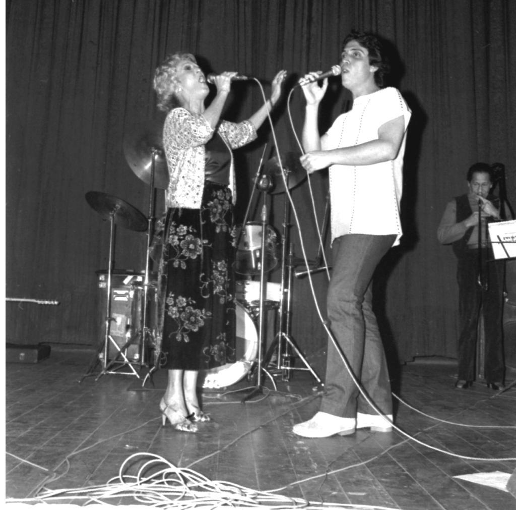 Audiodescrição da imagem: Fotografia quadrada, em preto e branco, de uma mulher e um homem cantando em um palco de auditório, com o acompanhamento de músicos ao fundo. Os dois cantores estão à frente, ao centro do palco, enquadrados por inteiro, posicionados para a fotografia mas voltados um para o outro. Eles têm a pele clara, seguram o microfone perto da boca, ambos com a mão direita, e estão concentrados na ação, com olhares dispersos um do outro. A mulher, à esquerda, é uma jovem senhora, magra, alta, com o cabelo claro, curto e cacheado. Veste uma blusa de Cetim e uma saia longa florida, ambos em tom escuro, um casaco até a cintura, em tom claro, com mangas até o cotovelo, e calça uma sandália de salto fino. Seu rosto está inclinado para cima e o braço esquerdo erguido, com o cotovelo dobrado e a mão aberta. O homem, à direita, é magro, ligeiramente mais alto que a mulher, com o cabelo escuro, curto, na altura do pescoço, e ondulado. Veste uma camiseta em tom claro, com linhas verticais espaçadas e pontilhadas, uma calça lisa em tom escuro, além de um calçado fechado, em tom claro. Tem o rosto sutilmente elevado e sua mão esquerda segura o cabo do microfone que utiliza. À frente dos cantores, ao chão, vê-se o emaranhado de cabos dos microfones e das caixas de som. Já atrás destes, à esquerda, o braço de uma guitarra/baixo, na horizontal, e um case para instrumentos musicais, deitado ao chão. Também se vê uma bateria atrás da jovem senhora. À direita, ainda ao fundo da imagem, uma estante com partituras e um jovem senhor, de frente para a fotografia, enquadrado por inteiro, lendo estas partituras e tocando um Trombone. O trombonista tem a pele e o cabelo em tonalidade escura, veste uma camisa social em tom levemente escuro, sobreposta por um colete, além de calça e sapato sociais também escuros. Atrás deste homem há uma caixa de som, em formato retangular, posicionada verticalmente, com dois grandes alto-falantes embutidos. Em todo o fundo da imagem, atrás das p