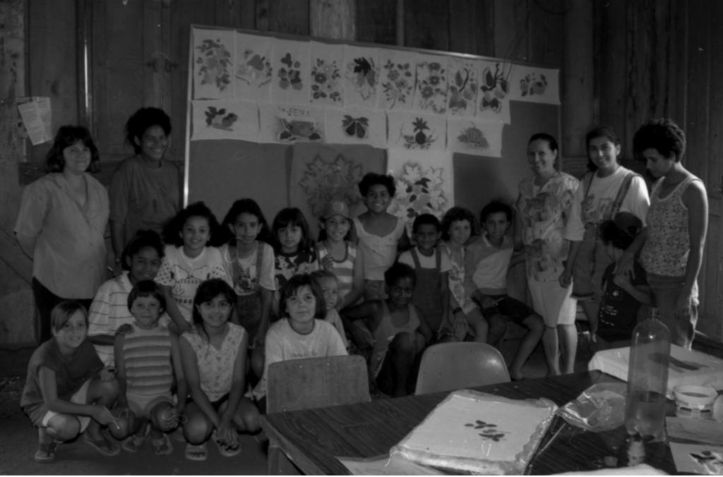 Audiodescrição da imagem: Fotografia horizontal, em preto e branco, de vinte e uma pessoas posando para serem fotografadas em um ambiente fechado. As pessoas estão enquadradas de corpo inteiro, de frente, sorriem e são na maioria crianças com faixa etária entre sete e doze anos. São quinze crianças organizadas em duas fileiras, ao centro da imagem, estando agachadas na frente e sentadas na fileira de trás, mais uma delas na lateral direita, em pé. Elas estão divididas entre meninos e meninas com tons de pele claro ou escuro, a maioria de cabelos curtos e escuros e vestindo macacões, vestidos, calções e camisetas de manga curta ou regatas e chinelos de dedo. Algumas seguram pincéis nas mãos. Além das crianças, há cinco mulheres, todas em pé. Na extremidade esquerda, uma mulher robusta, com o rosto redondo, pele em tom claro, cabelo em tom escuro, curto na altura do ombro e com franja reta dividida ao meio, vestindo camisa social larga com manga curta, em tom claro, e as mãos atrás das costas. À direita, uma jovem de rosto oval, pele em tom escuro, cabelo curto estilo Black Power, vestindo camiseta lisa de manga curta, larga e em tom escuro. Já na extremidade direita da imagem, mais três mulheres, da esquerda para a direita: uma mulher com rosto redondo, nariz longo, cabelo escuro em forma de penteado, vestindo camisa social de manga curta e estampada e saia social até os joelhos, ambas em tom claro; uma jovem, magra, com rosto redondo, cabelo preso, vestindo camiseta em tom claro e macacão jeans em forma de calção, tendo a mão esquerda sobre o ombro da criança que está em pé e vira-se para ela, ocultando o rosto; e uma mulher magra, com o rosto bem delineado, com a postura ligeiramente curva, de perfil esquerdo, com cabelo curto estilo Black Power, vestindo regata em tom claro e estampada e calça jeans. Em primeiro plano, ao canto inferior direito, parte da superfície de uma mesa de madeira, com duas cadeiras na lateral e, em cima, objetos como folhas de papel dentro