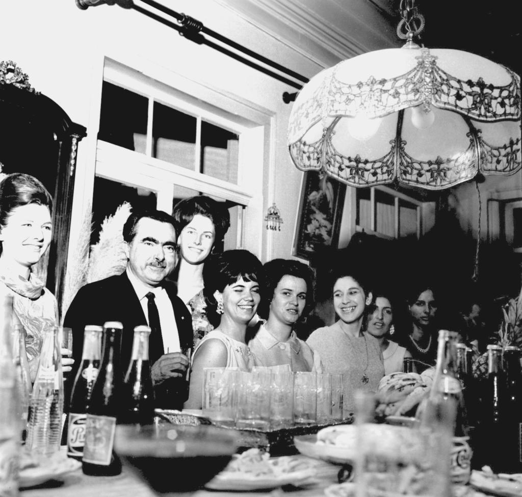Audiodescrição da imagem: Fotografia quadrada, em preto e branco, de oito pessoas enquadradas da cintura para cima, em um ambiente fechado e alto, como um salão antigo. Das pessoas, sete estão sentadas junto a uma mesa e uma está em pé, atrás dos demais. A imagem foi feita da esquerda para a direita, focando o tampo da mesa, na horizontal, com o canto de duas paredes, perpendiculares, ao fundo. As pessoas são seis mulheres e um homem, uma ao lado da outra, com algumas sorrindo, olhando para a frente ou ligeiramente voltadas à direita, estando uma inclusive de olhos fechados. Da esquerda para a direita, o homem é o segundo da fileira, tendo o rosto redondo com bochechas robustas, cabelo calvo mas vigoroso e escovado para trás e sobrancelhas grandes, ambos em tom escuro. Ele veste terno e gravata escuros e camisa social clara e segura um copo a frente, em sua mão direita. Das mulheres, incluindo a que está em pé as costas do homem, todas têm características em comum: jovens, magras, com traços finos, cabelos em forma de coque ou curtos e volumosos, usando adornos e roupas sociais como camisas e vestidos. Sobre a mesa, dois pratos com alimentos ao centro e várias garrafas de vidro dispersas, de diferentes bebidas, algumas cheias e outras vazias, além de uma bandeja com copos de vidro. Ao fundo, na parede da esquerda, duas grandes janelas verticais de madeira, tendo acima da janela da esquerda um varão de cortina; ao lado esquerdo, um espelho retangular com a parte superior em semicírculo; e ao lado direito, um quadro retangular e vertical na parede entre as duas janelas. Na parede da direita, a parte superior esquerda de uma janela. E no teto, por cima da mesa, um grande lustre de vidro na forma de uma flor virada para baixo, em tom claro com detalhes decorativos nas extremidades.